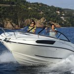 two women riding an outboard boat on a day time front view