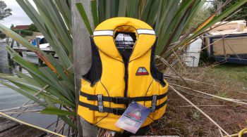 yellow life jacket hanging on a tree