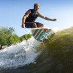 man wake surfing on a beach